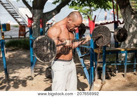 Powerlifter with strong arms lifting weights outdoor