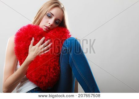 Broken heart love concept. Sad unhappy woman hugging red heart pillow closeup