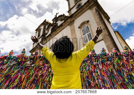 Local woman making a wish with the colorful religious brazilian ribbons in Salvador, Bahia, Brazil
