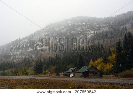 Abandoned Shotgun Shack Home in the Mountains with Snow and Clouds