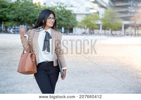 Cheerful beautiful businesswoman enjoying city life while walking over city. Happy purposeful young Hispanic lady carrying bag and laptop. Commuter concept