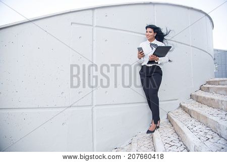Cheerful business lady always connectable. Smiling beautiful young Hispanic female manager using smartphone and holding laptop while walking over city. Technology concept