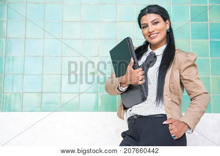 Cheerful female intern ready for work. Smiling confident Hispanic female manager holding closed laptop and looking at camera. Businesswoman or student concept