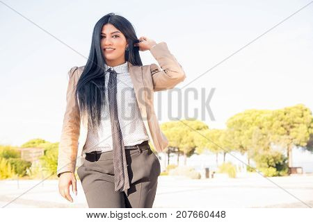 Cheerful successful business lady walking in park and enjoying good weather. Happy beautiful young woman adjusting hair and looking at camera. Life balance concept