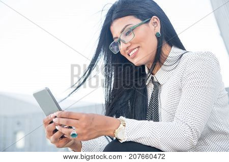 Cheerful young woman reading business news on phone or watching video on Internet. Positive beautiful Hispanic businesswoman using gadget outdoors. Mobile app concept