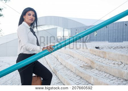 Confident female manager going to work and looking at camera. Serious elegant businesswoman leaning on railing while moving up stairs. Successful woman concept