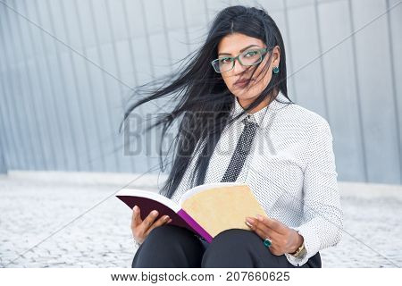 Confident smart woman reading business book and looking at camera. Serious beautiful businesswoman in eyeglasses interested in self-education. Student concept