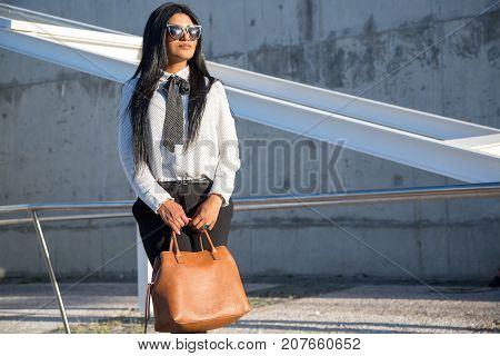Determined young businesswoman in sunglasses looking into distance and holding bag outdoors. Serious confident Hispanic lady dreaming of success. Fashion girl concept