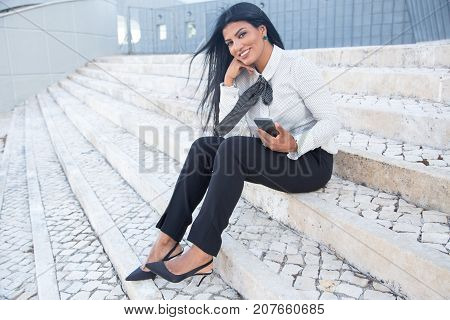 Happy beautiful woman sitting on stairs outdoors and looking at camera. Content pretty Hispanic businesswoman relaxing after work and using smartphone. Lifestyle concept