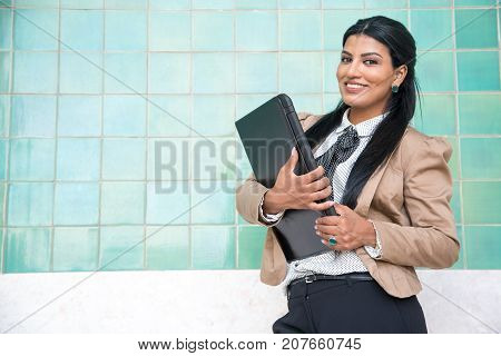 Happy modern student holding portable computer and looking at camera. Content successful businesswoman always taking laptop with her. Modern lifestyle concept