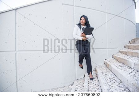 Pensive attractive businesswoman embracing laptop and looking at camera while leaning on wall, Serious confident Hispanic lady working everywhere. Life balance concept