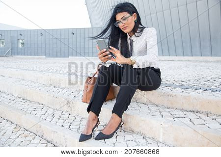 Pleased businesswoman responding to sms on phone while sitting on stairs outdoors. Serious young Hispanic manager texting message on smartphone. Technology concept