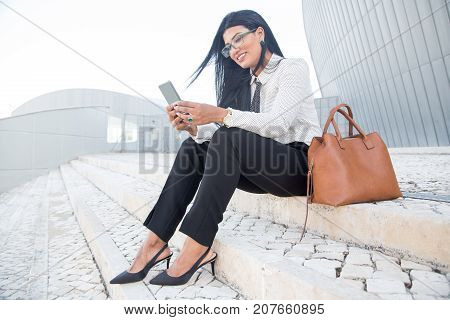 Positive young businesswoman using gadget for work while resting on stairs. Cheerful busy lady smsing via smartphone. Mobility concept