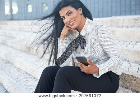 Smiling stylish businesswoman looking at camera and sitting on stairs alone. Cheerful beautiful female manager with hair blown by wind always connectable. Mobility concept