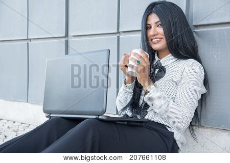 Successful freelancer enjoying work outdoors and looking at camera. Happy young Hispanic businesswoman drinking coffee and using portable computer while sitting on ground. Modern lifestyle concept