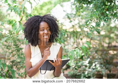 Closeup portrait of smiling young attractive black woman working, making notes in park