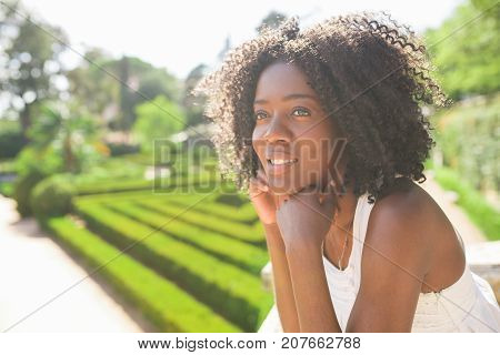 Closeup portrait of smiling young attractive African American woman standing and leaning on railing in park with blurred beautiful garden in background. Side view.