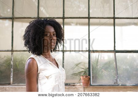 Portrait of serious young African-American woman wearing white blouse standing at window and looking at camera. Beauty concept