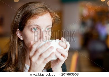 Closeup portrait of pensive attractive young woman holding cup with both hands and drinking coffee or tea with blurred view in background