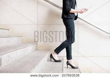 Cropped view of business woman holding tablet computer and walking down stairs outdoors with wall in background. Side view.