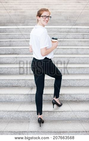 Portrait of business woman turning round, looking at camera, holding disposable cup and climbing up stairs outdoors. Back view.