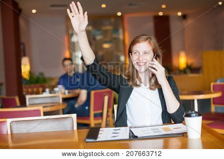 Closeup portrait of smiling attractive young woman working, raising arm, calling waiter, talking on smartphone and sitting at table in cafe with blurred interior and visitors in background