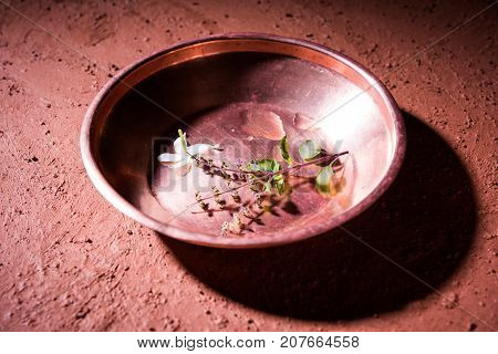copper kalash, glass, spoon and plate used by Bramhins after sacred thread ceremony while performing Sandhya Vandanam or Sandhya Kriya, over clay background with tulsi or basil leaves & flowers