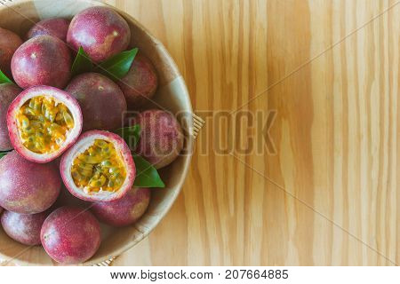 Fresh passion fruit in wood bowl on wood table in top view flat lay with copy space for background or wallpaper. Ripe passion fruit so delicious sweet and sour. Passion fruit is tropical fruit. Passion fruit background concept.