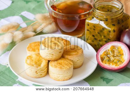 Homemade plain scones serve with homemade passion fruit jam. Scones is traditional English pastry for afternoon tea or coffee break. Delicious plain scones with homemade passion fruit jam ready to served on wood table.