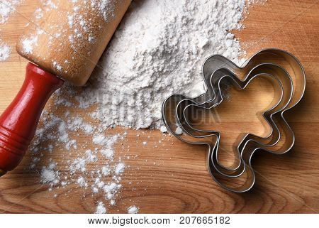 Closeup top view of a rolling pin on a cutting board with flour and gingerbread man cookie cutters.