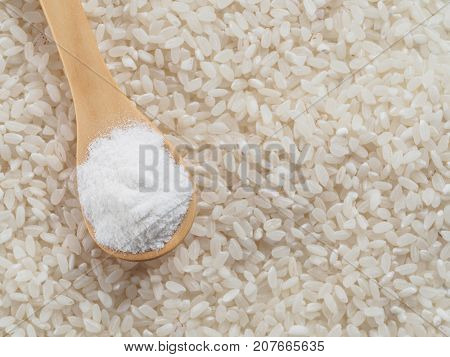 rice flour in wooden spoon and rice grains. whole-grain rice flour on rice grains background. Copy space. Top view or flat lay.