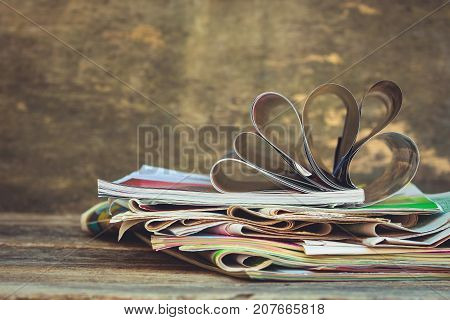 Newspapers and magazines on old wood background. Toned image