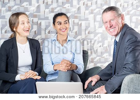 Laughing young lesbians meeting with tax advisor to discuss their finance. Cheerful consultant showing file on laptop during meeting. Psychotherapy concept
