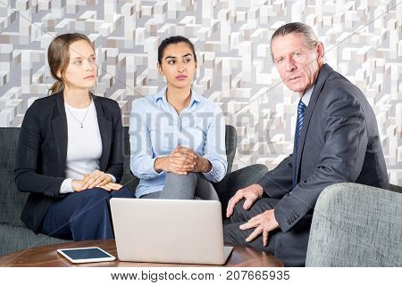 Serious lawyer holding consultation for girls. Unsmiling psychologist working with lesbians at meeting. Business colleagues discussing strategy. Meeting with realtor concept