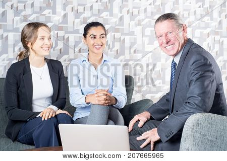 Cheerful lesbian couple consulting with real estate agent in office. Smiling senior manager helping client to choose house. Meeting with specialist concept