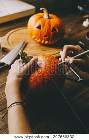 Girl worked on wooden table with pampkin for halloween
