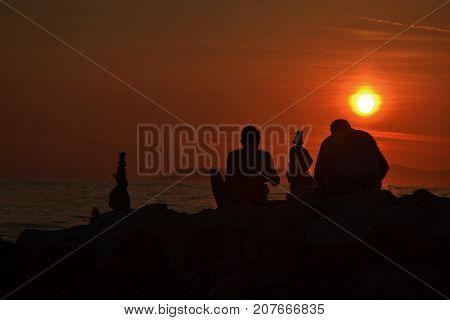 Sunset at the beach whit silhouettes of people