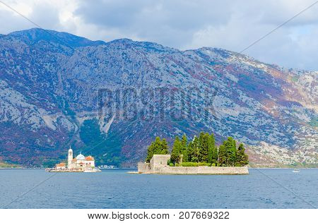 Island of Virgin on reef (Island Gospa od Skrpela) and Island of St. George (Island of Dead) against background of mountains Bay of Kotor Montenegro