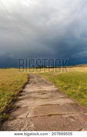 Country road to the storm. Autumn evening with black clouds. The dark sky before the storm