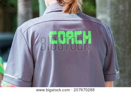back of a coach's grey shirt with the green word Coach written on it compose to leave space on left side for text or graphics good background for sport or coaching theme