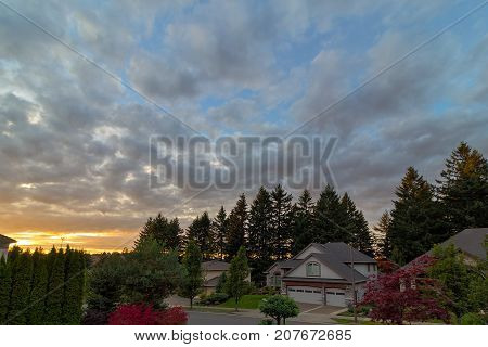 Sunset over street of suburban neighborhood of luxury upscale homes in North America