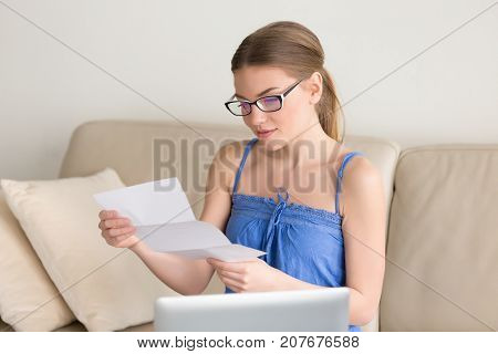 Young woman holding letter sitting near laptop on couch, looking at paper in hands with light smile, checking post correspondence at home, reading good news in mail, receiving medical test results
