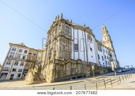 Side view of majestic baroque Church of Clerigos or Igreja dos Clerigos, in Portuguese, and iconic Clerigos Tower, one of the landmarks and symbols of Oporto city in Portugal. Sunny day with blue sky.