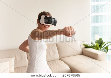 Young teen gamer wearing augmented reality glasses standing in boxing stance playing action simulator game mobile app, female player fighting with fist in VR headset, virtual training new technology