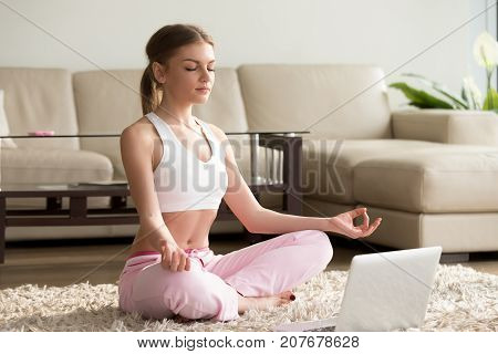 Young calm woman sits in staff easy lotus pose near laptop at home interior, meditating alone on the floor with eyes closed, online yoga training, doing breathing exercise in the morning, no stress
