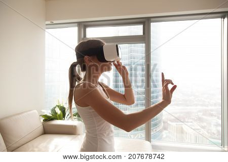 Young woman experiencing immersive virtual reality technology wearing VR glasses, interacting with 360 degrees headset user interface, choosing goods while shopping, selects content in 3d gaming menu