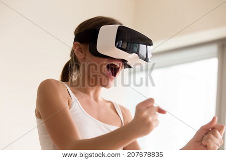 Young female gamer in wearable VR headset playing action 3d video game at home, excited teen holding wheel and screaming driving digital racing car in simulator application, virtual gaming concept