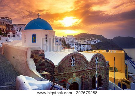 Amazing sunrise at Oia town on Santorini island, Greece. Traditional and famous houses and churches with blue domes over the Caldera, Aegean sea