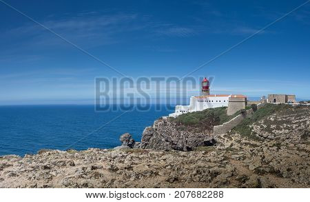 Panoramic picture of Cabo de Sao Vincente Cape Saint Vicent lighthouse on the rocks above the Atlantic ocean. The most south-western point of Europe. Sagres Algarve region Portugal. Sunny panoramic picture with clear blue sky