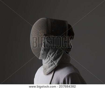 Profile of a fencer in fencing mask.Studio shot